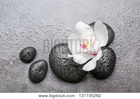 Spa stones and white orchid on grey background