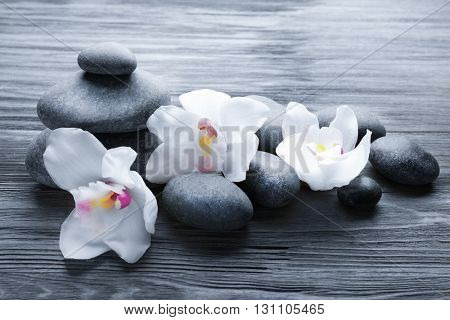 Stones and white orchid on wooden background