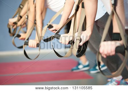 Close up of female hands leaning on the trx fitness straps. The group of girls are standing and doing push-ups