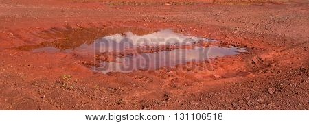 pudddle in trail on red land of Krivyi Rih, Ukraine
