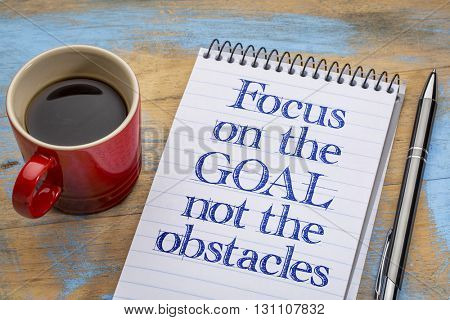 Focus on the goal, not the obstacles - inspirational advice on a spiral notebook with a cup of coffee
