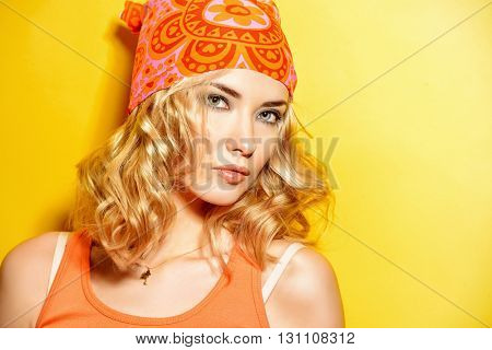 Pretty girl with curly blonde hair wearing bright clothes posing over yellow background. Bright style, fashion.