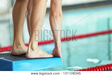 Legs of sporty young man preparing to jump into the water in the swimming pool, close-up