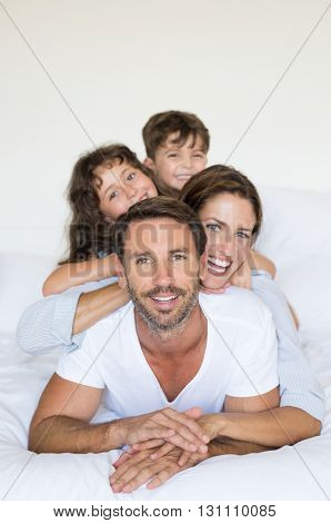 Happy smiling family lying on white bed. Young parents lying with son and daughter in bed having fun together. Happy young family making a human pyramid and looking at camera.