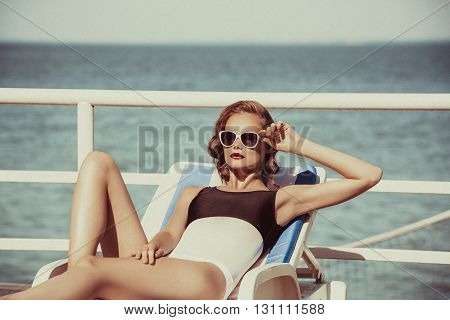 Beautiful brown hair woman wearing bikini. Young girl model in sunglasses and elegant black and white sexy swimsuit lingerie near swimming pool with clear blue water, . Full relax. Vintage. Sunbathe.