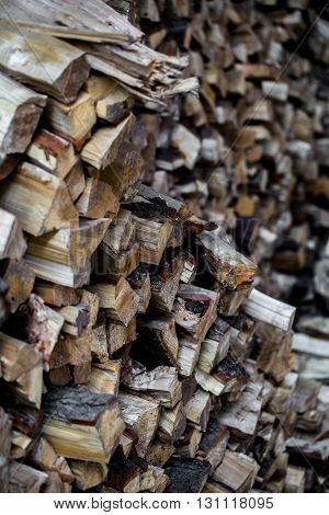 a very large pile of firewood stacked in an old barn