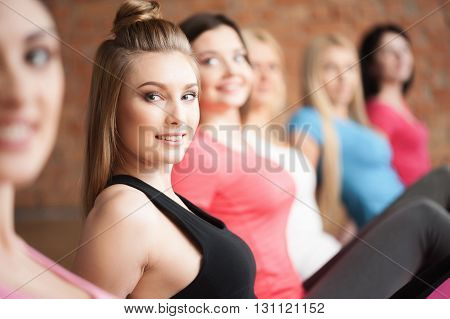 Pretty female sporty group is exercising in gym. The women are sitting in pose and smiling
