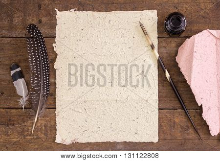 Photo of handmade blank paper quill pen and ink or rustic wood desk