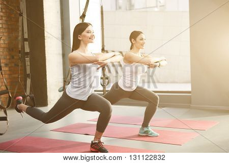 Beautiful young two girls are training with trx fitness straps. They are doing sit-ups and stretching leg behind. Their arms are crossed. The ladies are smiling