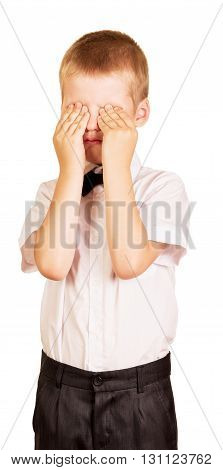 Crying boy covers his face with hands isolated on white background.