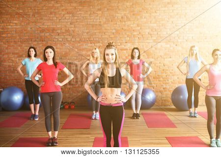 Attractive young women are doing exercise in gym. They are standing with arms akimbo. The ladies are smiling