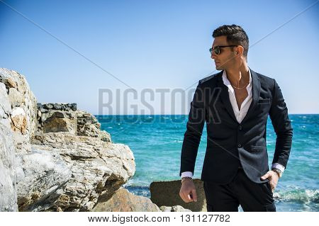 Young handsome man in classical suit on beach holding sunglasses while looking away. Sea waves on background