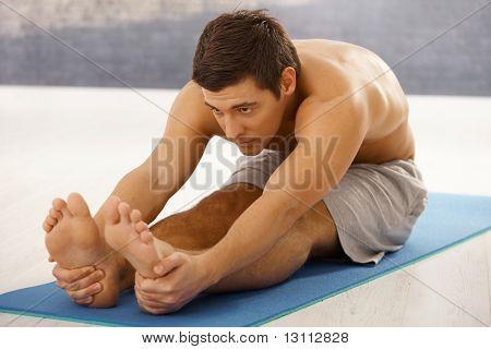 Gut aussehend athletischen Kerl stretching für Training auf Schaumstoff-Matratze im Gym.?
