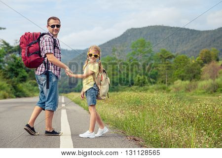 Father and daughter walking on the road at the day time. Concept of friendly family.