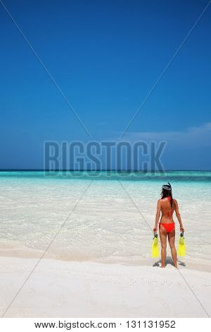 Woman in snorkeling gear stands on a tropical beach and watches the ocean