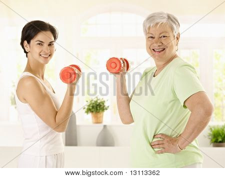 Healthy senior woman doing dumbbell exercise with personal trainer at home, smiling.?