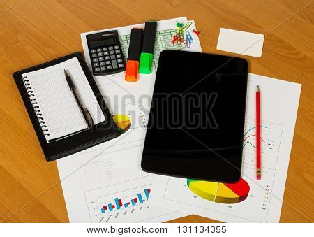 Calculator, tablet, notebook and other stationery to the desktop background.