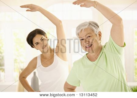 Healthy elderly woman doing exercises with personal trainer at home, smiling.?