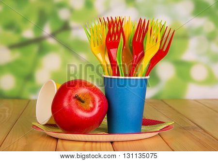 Bright disposable tableware and apple on an abstract green background.