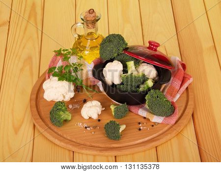Pan with cauliflower, broccoli, bottle of oil and spices on a background of light wood.