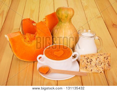 A cup of pumpkin puree, a jug of milk and cookies on light wood background.