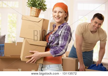 Happy couple carrying boxes at moving house.