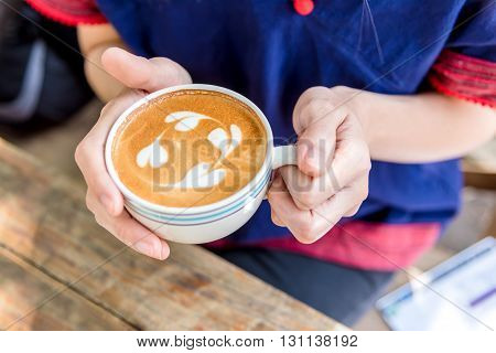 hand holding coffee cup above wooden table top view coffee cup