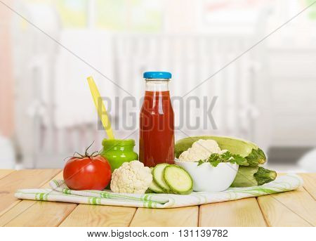 A bottle of tomato juice and vegetable puree bank with cauliflower and zucchini on the background of the kitchen.