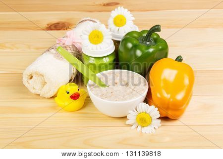 Baby food: a bowl of oatmeal, cans of vegetable puree, pepper, cotton towel and a rubber duck on a background of light wood.