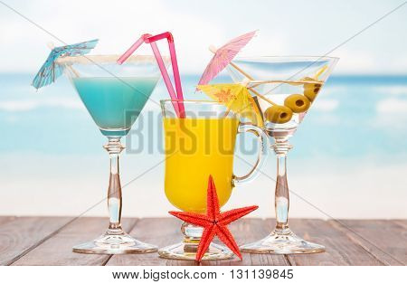 Two cocktails, a glass of juice and starfish on a sea background.