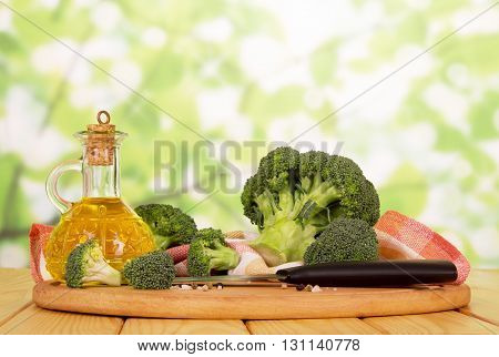 Fresh broccoli, oil in glass bottle, spices, knife and towel on abstract green background.