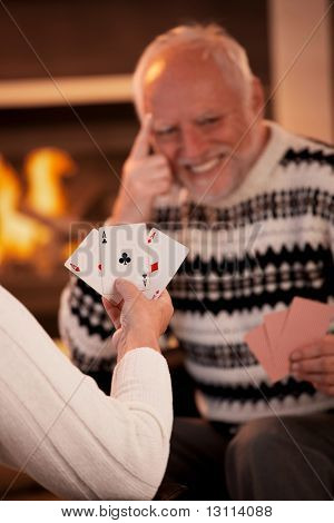 Playing cards in front of fireplace, senior man laughing in background, focus on female hand holding winning cards, three ace.