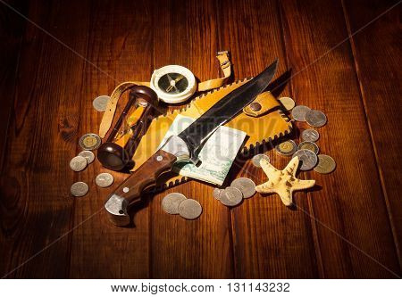Accessories for the traveler: the compass, an hourglass, knife and money on a background of dark wood.