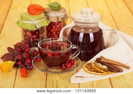 Banks hawthorn berry, rose, pitcher drink a cup of tea, cinnamon sticks and slices of lemon on a background of light wood.
