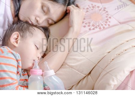 Baby milk bottle and water bottle holdind by asian baby boy. Asian baby boy sleeping in mother arm