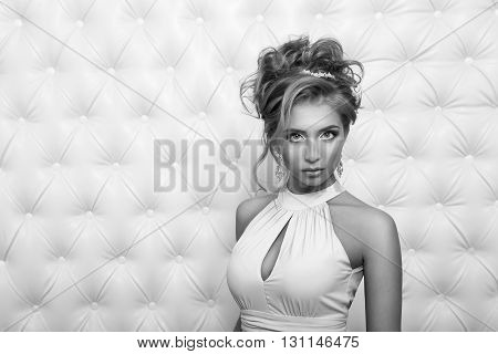 Studio portrait of a sexy blond in dress, over leather upholstery background. Elegant luxury woman with a seductive neckline and bare shoulders looks into the camera.