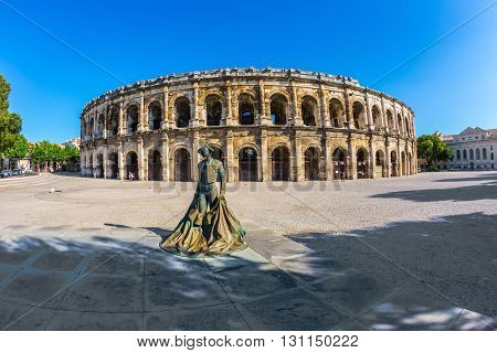 Monument to bullfighter installed before the arena. Roman amphitheater in Nimes, Provence. Photo taken fisheye lens