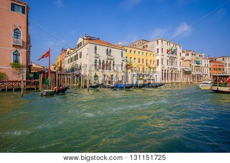 VENICE, ITALY - JUNE 18, 2015: Nice little port on Venice, people and tourists take this boats as a tranportation. Typical achitecture.