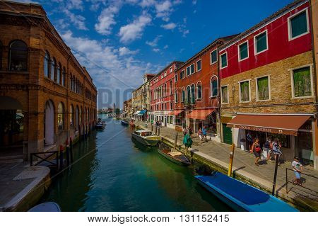 MURANO, ITALY - JUNE 16, 2015: Murano main canal in a sunny day, water as a mirror and boats on the sides.