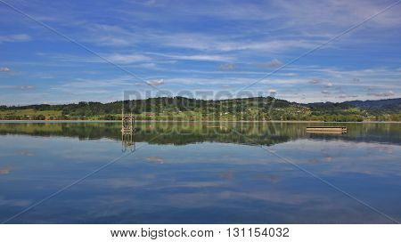 Green hills mirroring in Lake Pfaffikon. Spring scene in Zurich Canton Switzerland.