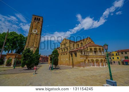 MURANO, ITALY - JUNE 16, 2015:  Spectacular view in a sunny day of Murano s Cathedral, Santa Maria e San Donato with the clock tower.