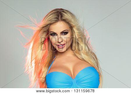Smiling beautiful blonde girl posing in bikini studio shot.