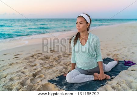 Yoga mat woman stretching hip, hamstring muscles and groin area, leg muscles with pigeon pose stretch. Fit Asian fitness athlete girl exercising sports stretches in activewear on beach at sunset. poster