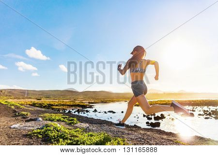 Athlete runner trail running on summer trail beach. Active morning jogging motivation woman sprinting with energy and motion in outdoors nature training cardio race in shorts and sports bra, shoes.