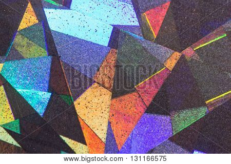 Colorful geometric patterns formed by light reflecting off a textured metallic surface