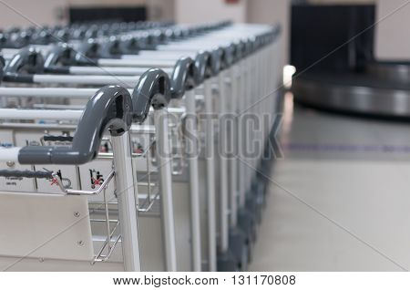 Selective focus of stack of trolley line at the airport with grey handgrips polycabonate's trolley