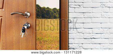 Entrance door half opened to nature background. Door handle, door lock. Exit outdoors. Opening door. Entrance to the house. Door at white brick wall, summer field and forest, freedom concept.