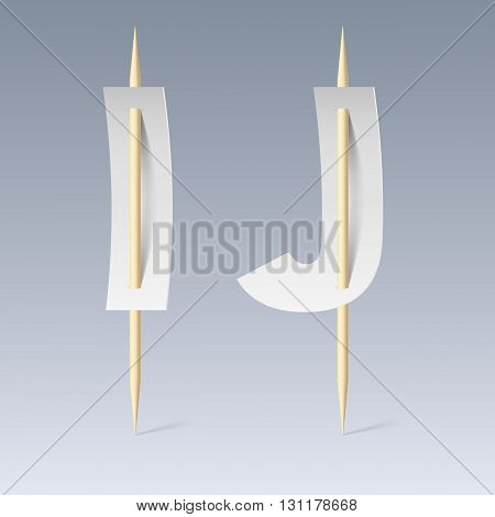 White paper cut font on toothpicks on grey background. I and J letters