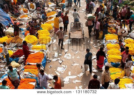 KOLKATA, INDIA - JAN 11, 2013: Crowd of people buy and sell flowers in Mullik Ghat Flower Market on January 11, 2013. The market is more than 125 years old. More than 2000 sellers work in the market every day