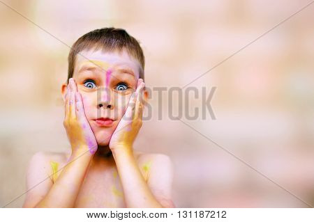 child with painted face very surprised. cute boy with a face stained with paint eyes widened in amazement. copy space for your text
